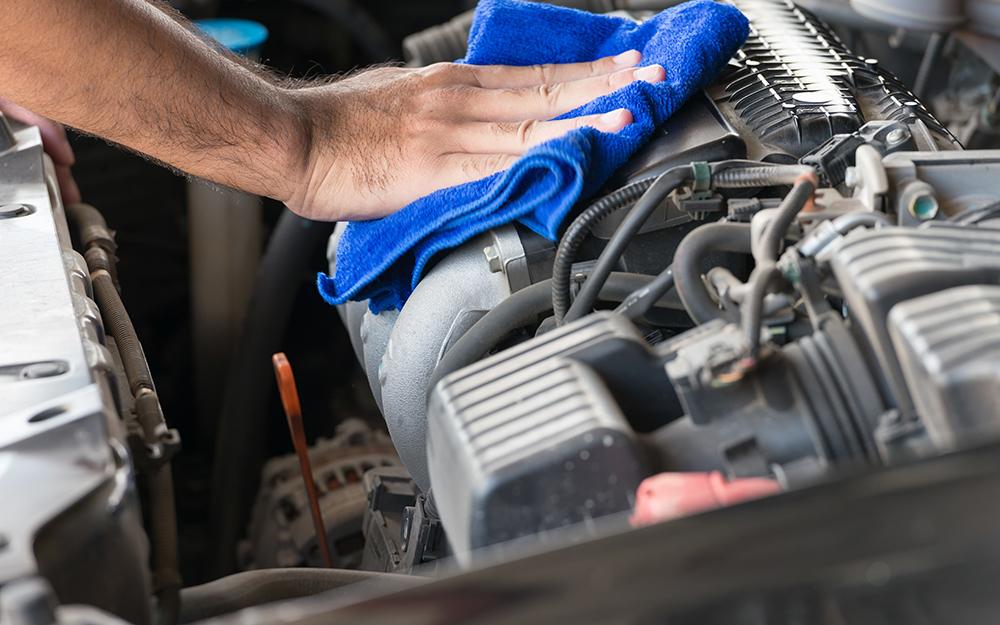 Một người dùng khăn lau sạch khoang động cơ của ô tô.
