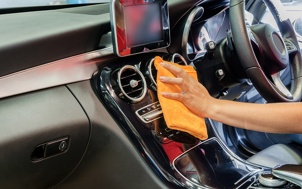 Một người dùng khăn lau bảng điều khiển của ô tô.
