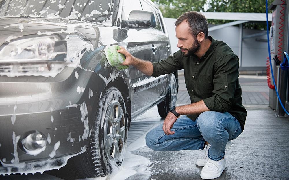 Một người dùng miếng bọt biển rửa bên ngoài ô tô.