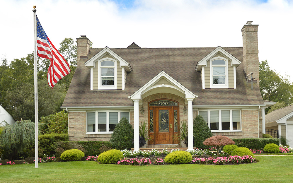 American flag displayed on a flagpole in front of a home.