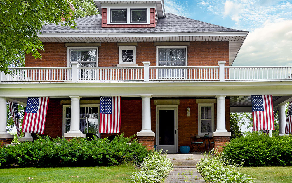 American flags hanging horizontally around a home's porch.