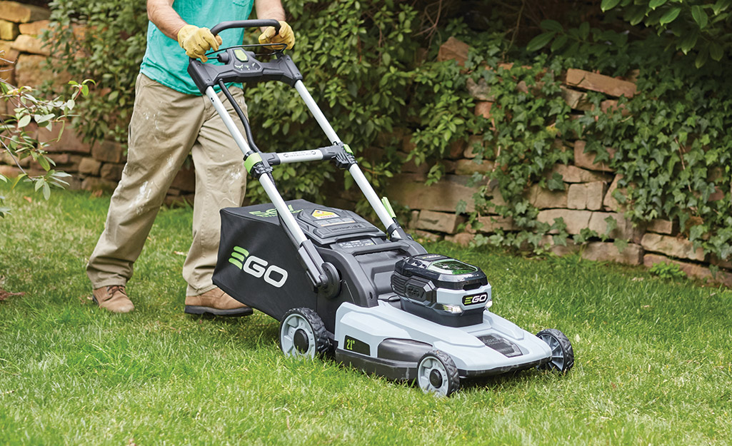 Someone using an electric edger to trim the grass beside a walkway.