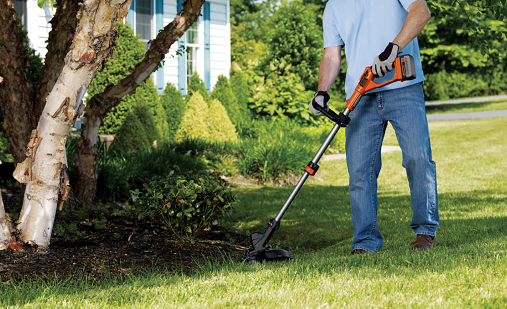 A person using a power edger to trim the grass.