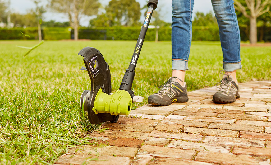 Someone using a cordless edger to trim the grass along a brick walkway.