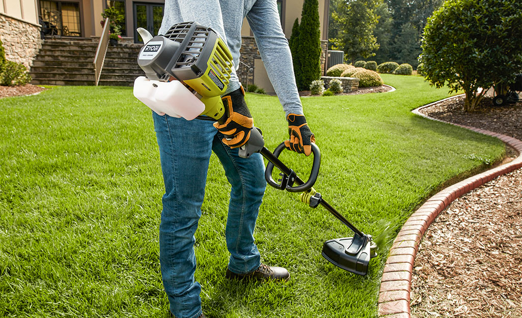 A person using a gas string trimmer along a mulched bed.