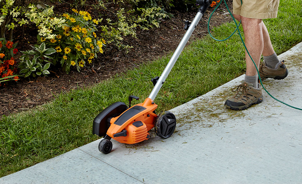 Someone using a cordless edger to trim hedges and edge a lawn.