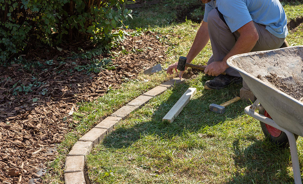 A person making a curved paver border near trees.
