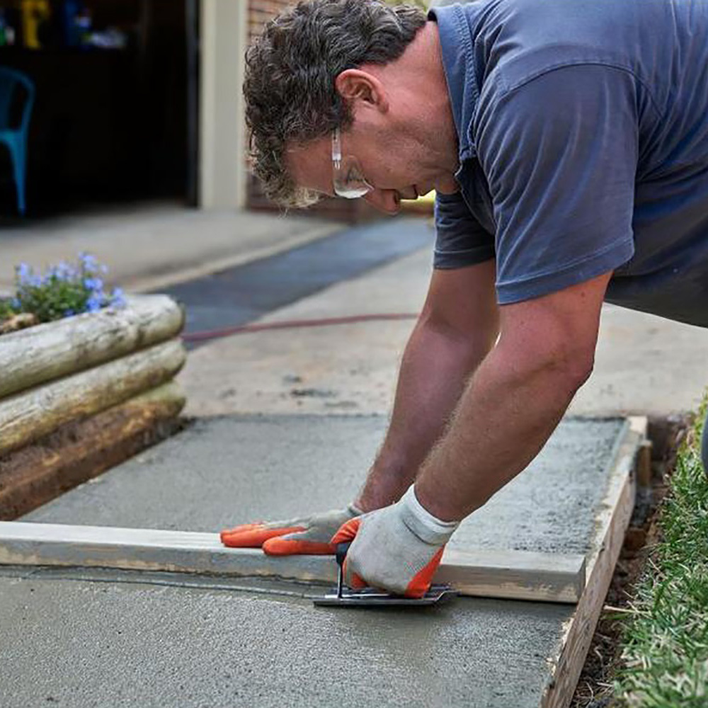 A man using a board and a float to smooth just-poured concrete.