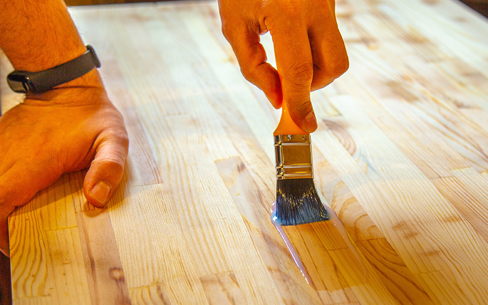A person applying a clear finish to a wood tabletop.
