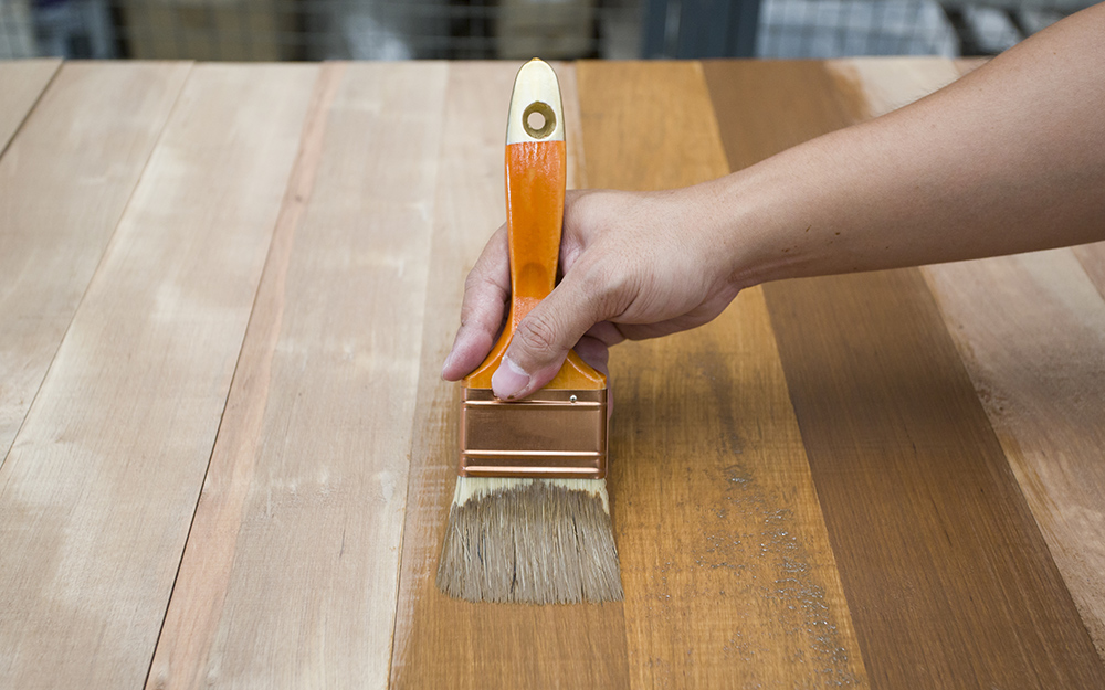 A person brushing stain onto a table.