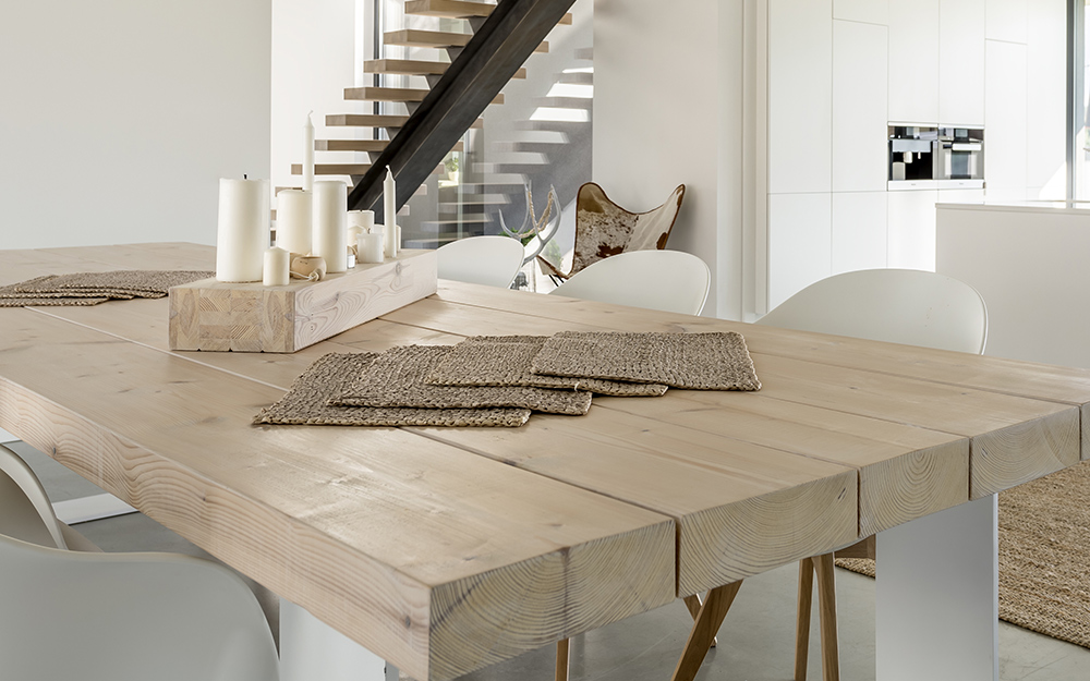 A table with a natural wood finished top and white painted legs.