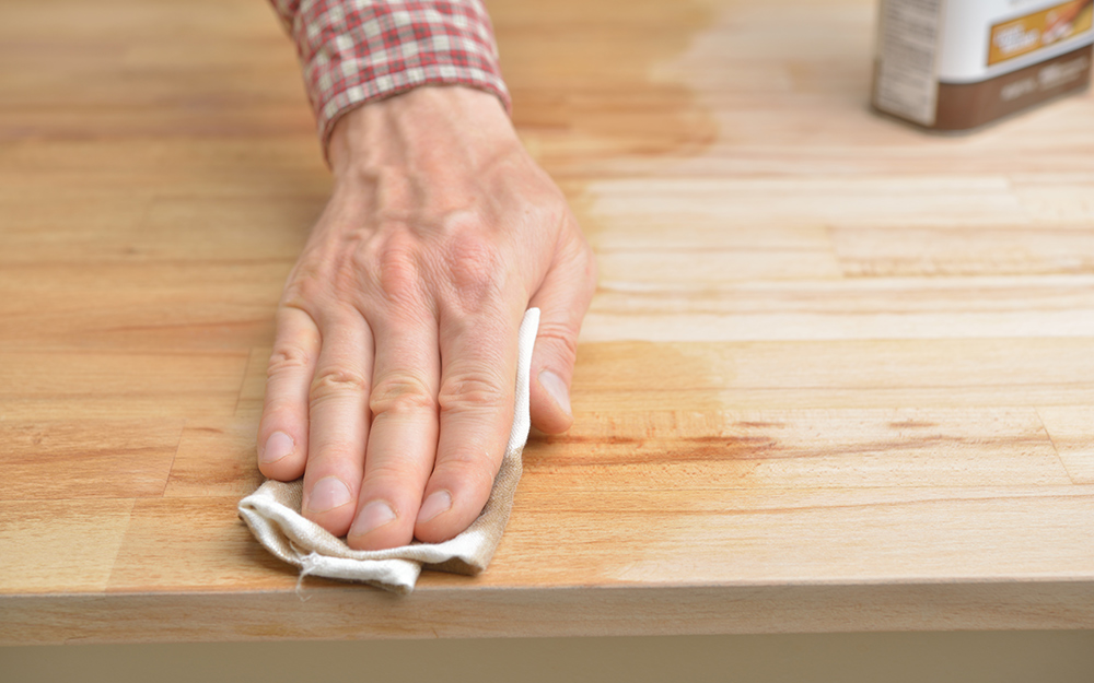 A person rubbing oil into wood.
