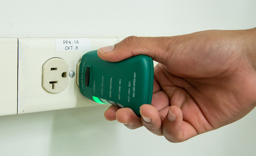 A hand holds a circuit tester inserted into a wall outlet.