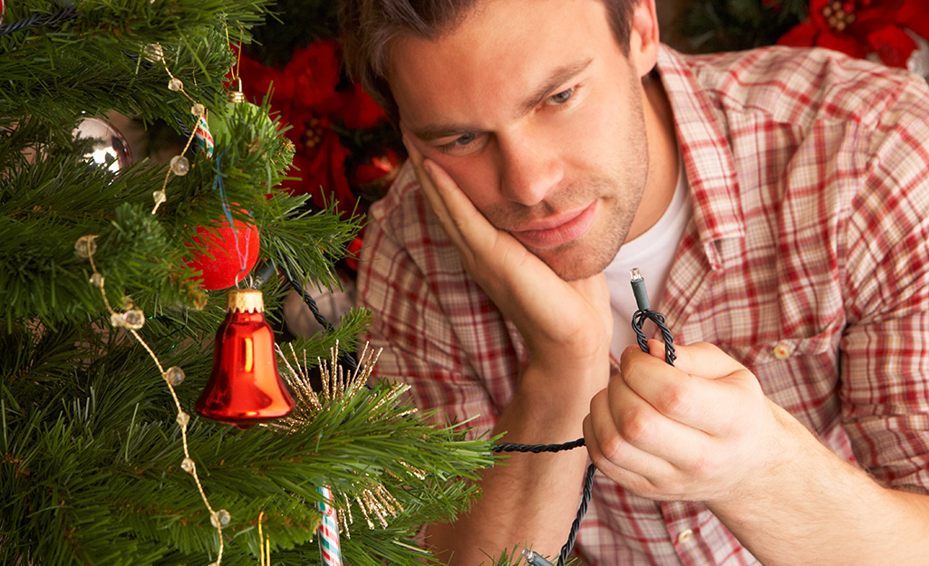 Man contemplates a single unlit bulb on a strand of Christmas tree lights.