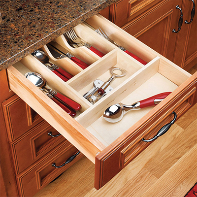 An open kitchen drawer with utensils displayed in slots.