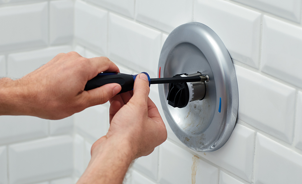 A person uses a tool to unscrew a bathtub handle.