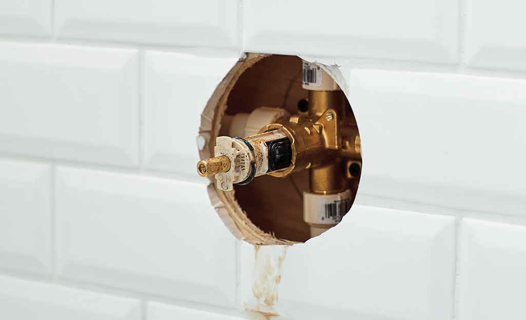 A bathtub faucet with the internal parts exposed.