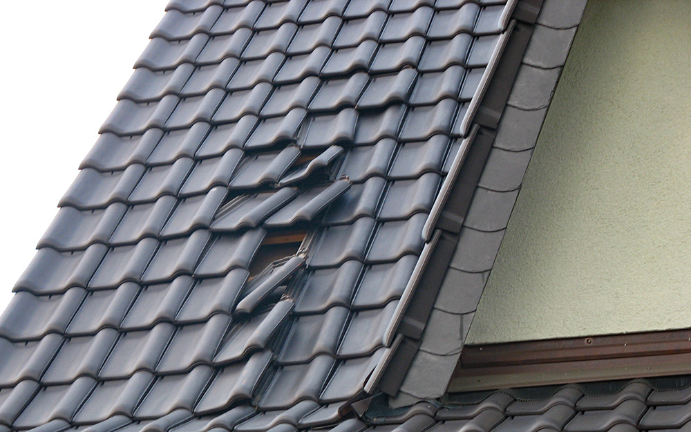 Roofing material on a house appears damaged or improperly installed.