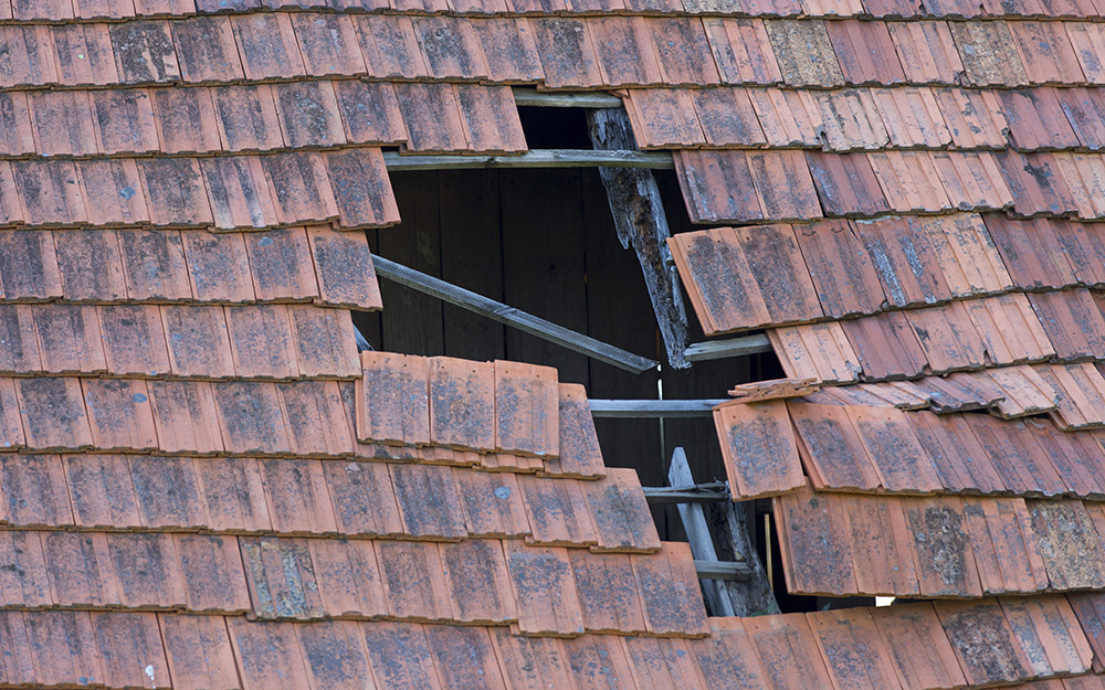 A damaged roof with an exposed hole is in need of repair.