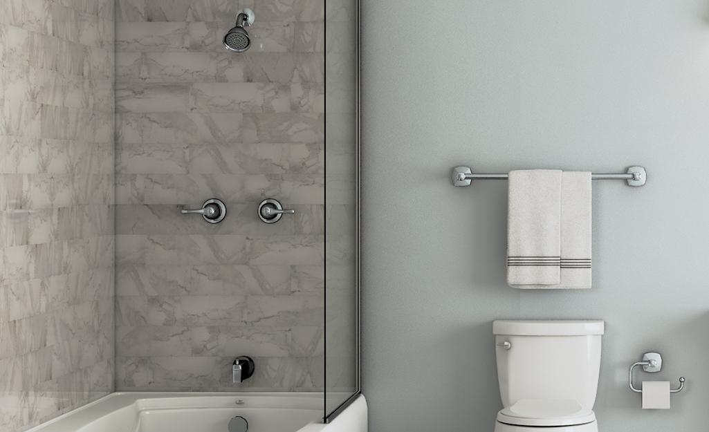 Phòng tắm màu trắng và xám với góc tắm vòi sen, bồn tắm, giá treo khăn tắm và toilet.