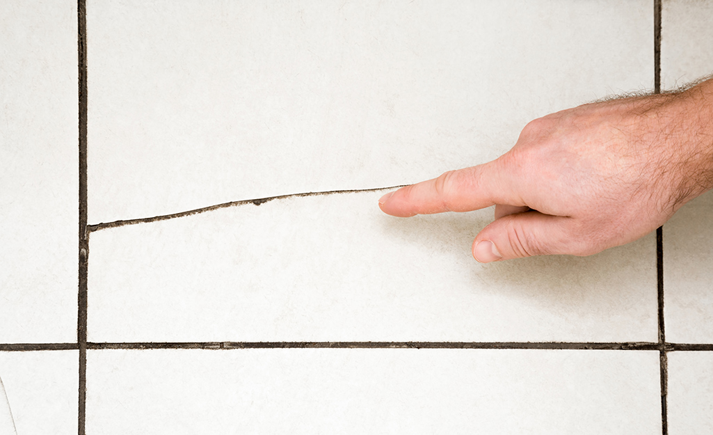 A person pointing to a small crack in a piece of tile.
