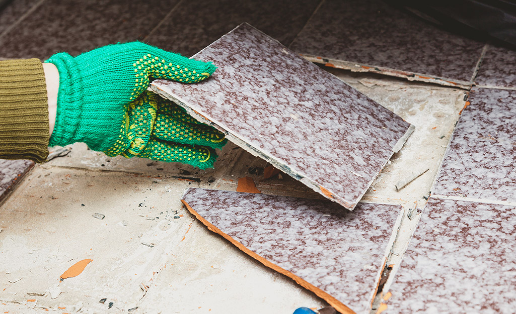 A person removing pieces of broken tile from a floor.