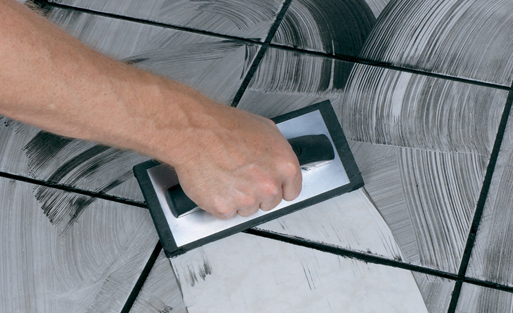 A person applying grout to a tile floor.