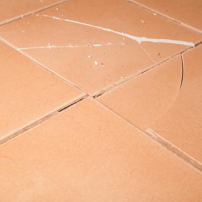 A couple of cracked floor tiles next to unbroken ones.