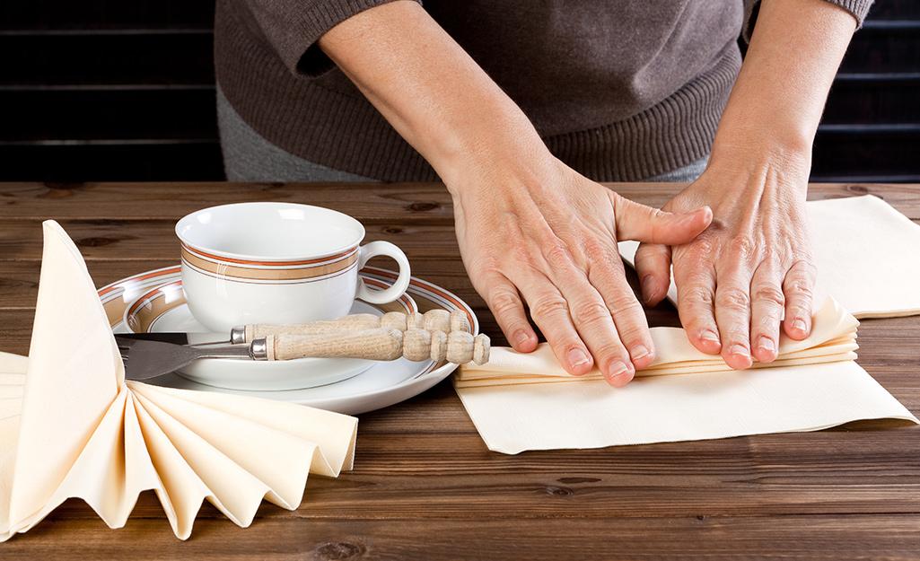 Một người làm khăn ăn gấp quạt trên bàn.