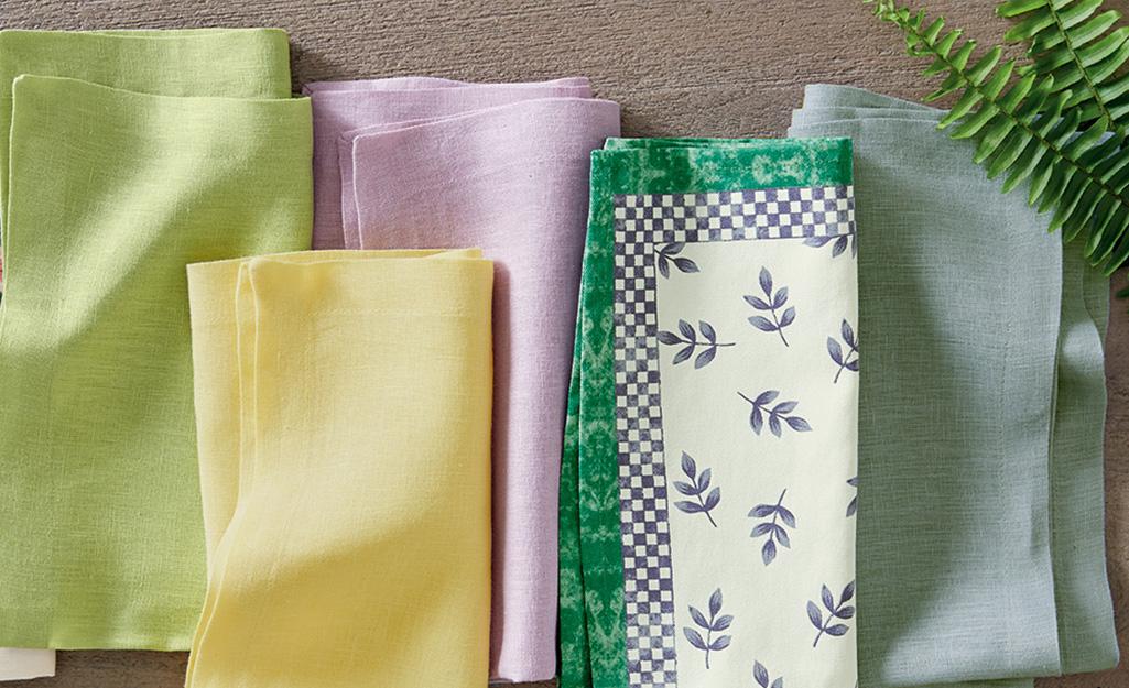 Nhiều loại khăn ăn bằng vải màu được xếp lỏng lẻo trên bàn.