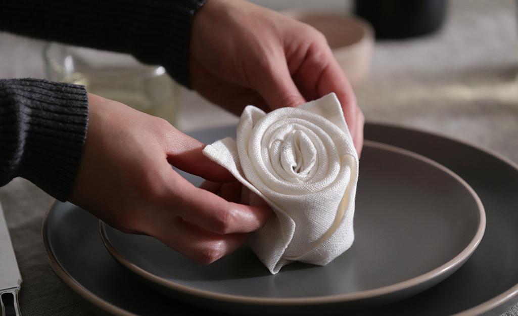 Một người hoàn thành việc gấp khăn ăn hoa hồng trên đĩa ăn tối.
