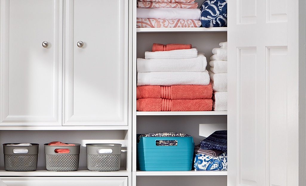 Colorful towels on shelves in a linen closet.