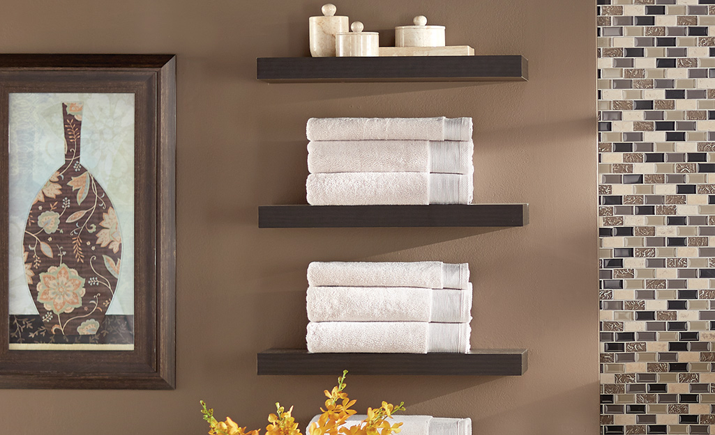 Folded white towels on floating wood shelves in a bathroom.
