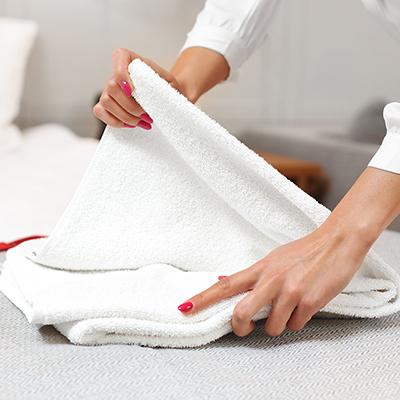 A person folding a white towel.