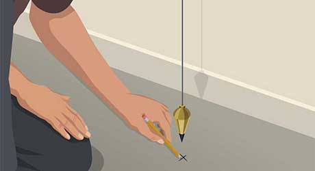 A person using a pencil to mark a spot on the floor underneath a plumb bob