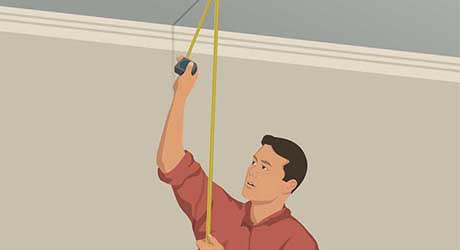 Person measuring stud length between ceiling and floor with tape measure