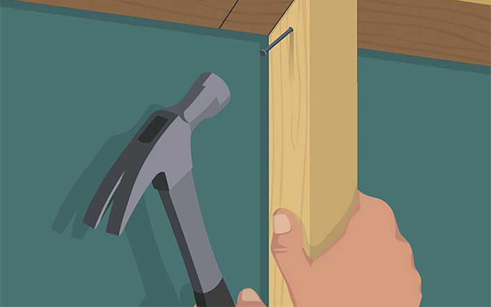 illustration of a person hammering a nail into the king studs of a door frame