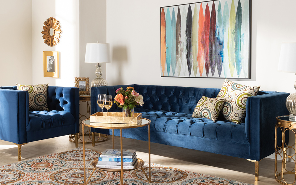 Một chiếc ghế sofa nhung màu xanh và chiếc ghế thư giãn trong phòng khách.