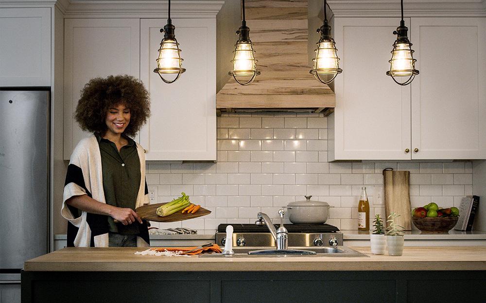 Một người phụ nữ nấu ăn trong căn bếp nhỏ của căn hộ.