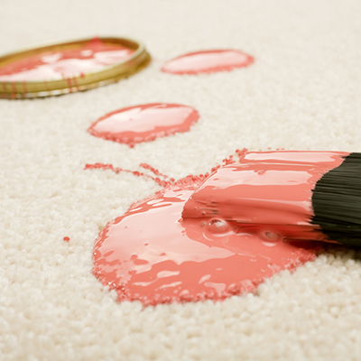 A paint brush soaked in pink paint spilled on a white carpet.