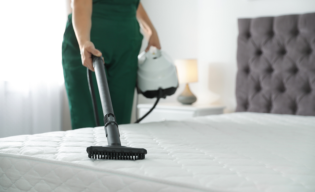 Person vacuuming their mattress.