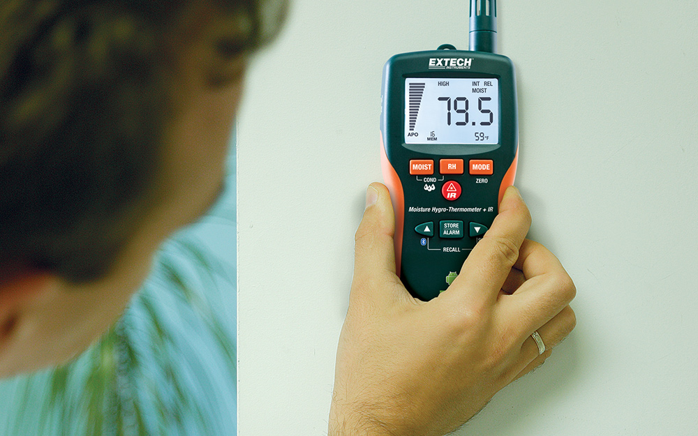 A person holding a moisture meter against a wall