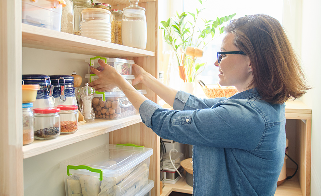 Person placing containers of food on a shelf.