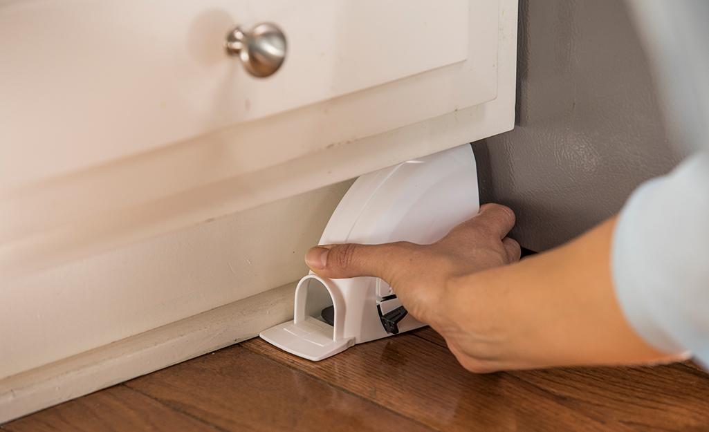 Une personne place un piège à souris fermé sous une armoire de cuisine.