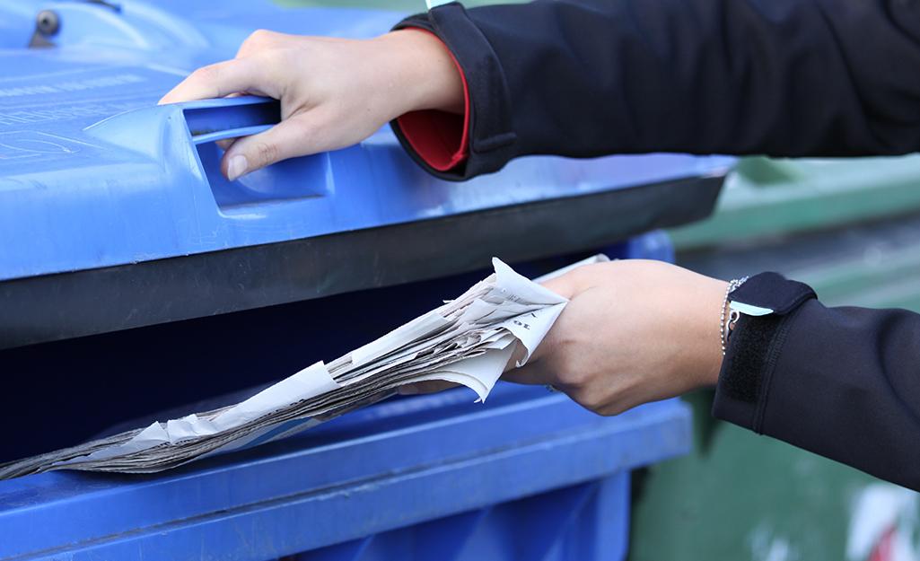 Une personne recyclant de vieux journaux.