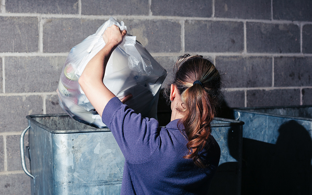 A person disposing of a large bag of trash.
