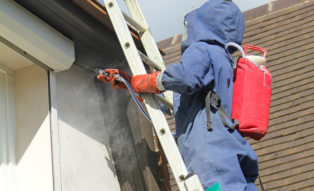 Person on a ladder spraying chemicals outside their home.