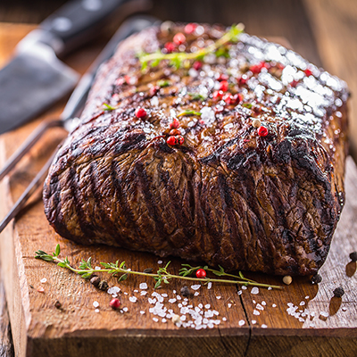 A grilled steak rests on a cutting board.