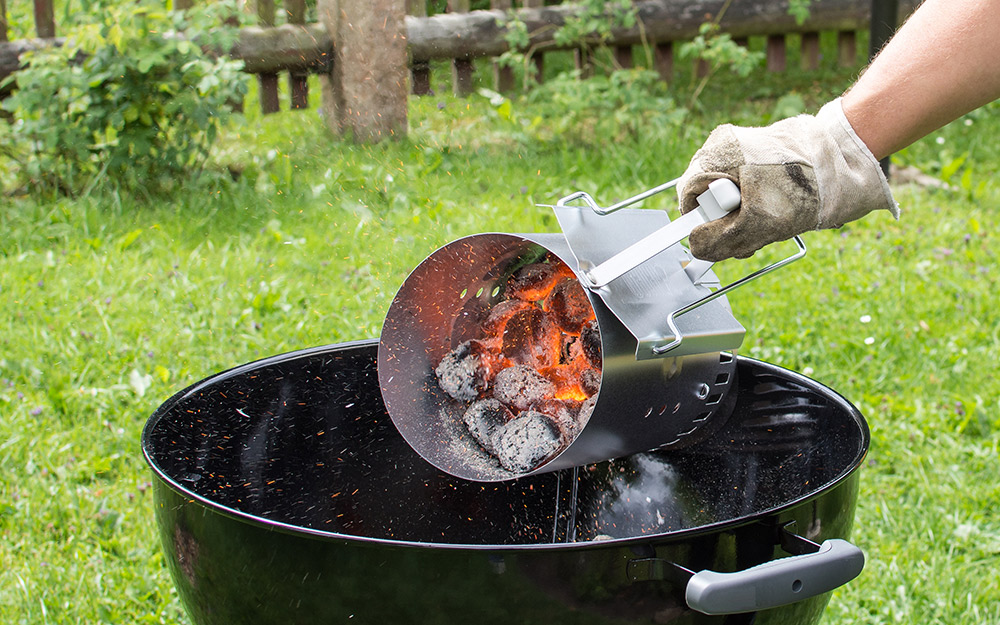 A person pours hot coals into one side of a kettle grill.