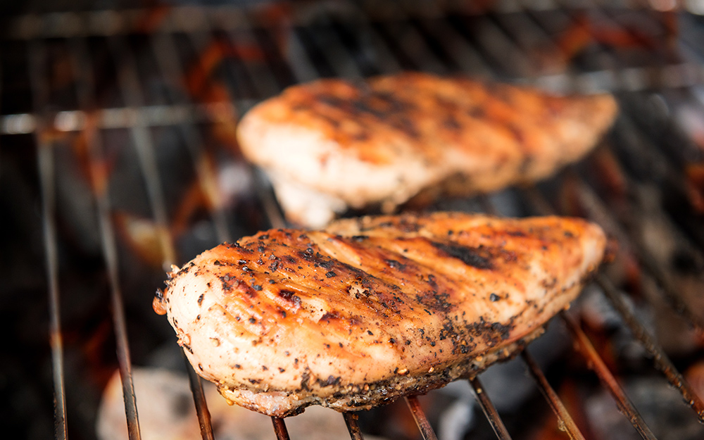 Pieces of chicken cooking on a hot grill.